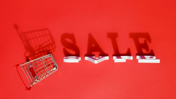 Small empty shopping trolley cart, word SALE and falling white letters casts a large shadow, on red background. Concept sale. Creative template for your text, design, ad or advertisement