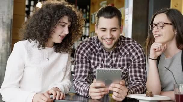 Různorodá skupina mladých přátel drží Tablet směje kavárna studentů studujících při pohledu na legrační Meme videa Slow Motion výstřel na Red Epic 8k