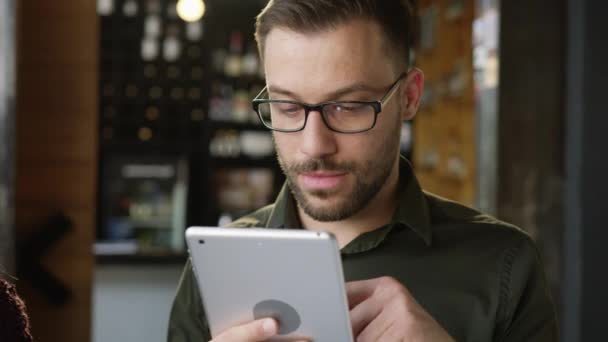 Attractive Trendy Yung Man Using An iPad In A Cafe Bar Researching Project Reading Online Article Developing Online Application 4G Connection Concept Slow Motion Shot On Red Epic 8K