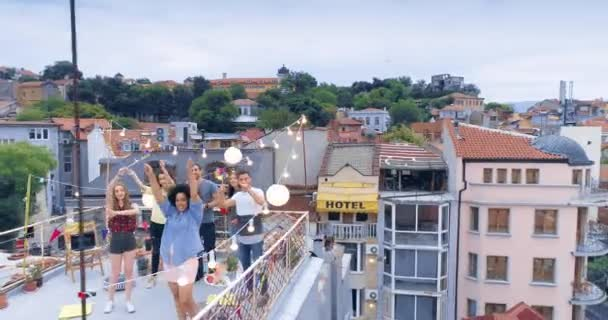 Aerial Flight Over Diverse Group Of Young People On Rooftop Celebrating And Waving Hands Bonding Summer Vacation Leisure Time And Relaxation Concept At Sunset