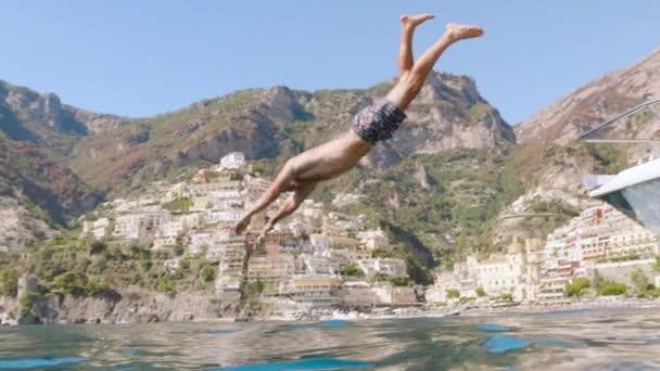 Pohledný mladý muž skočil z jachet Fitness Backflip Athlette Slow Motion podvodní záběr červené epické 8k