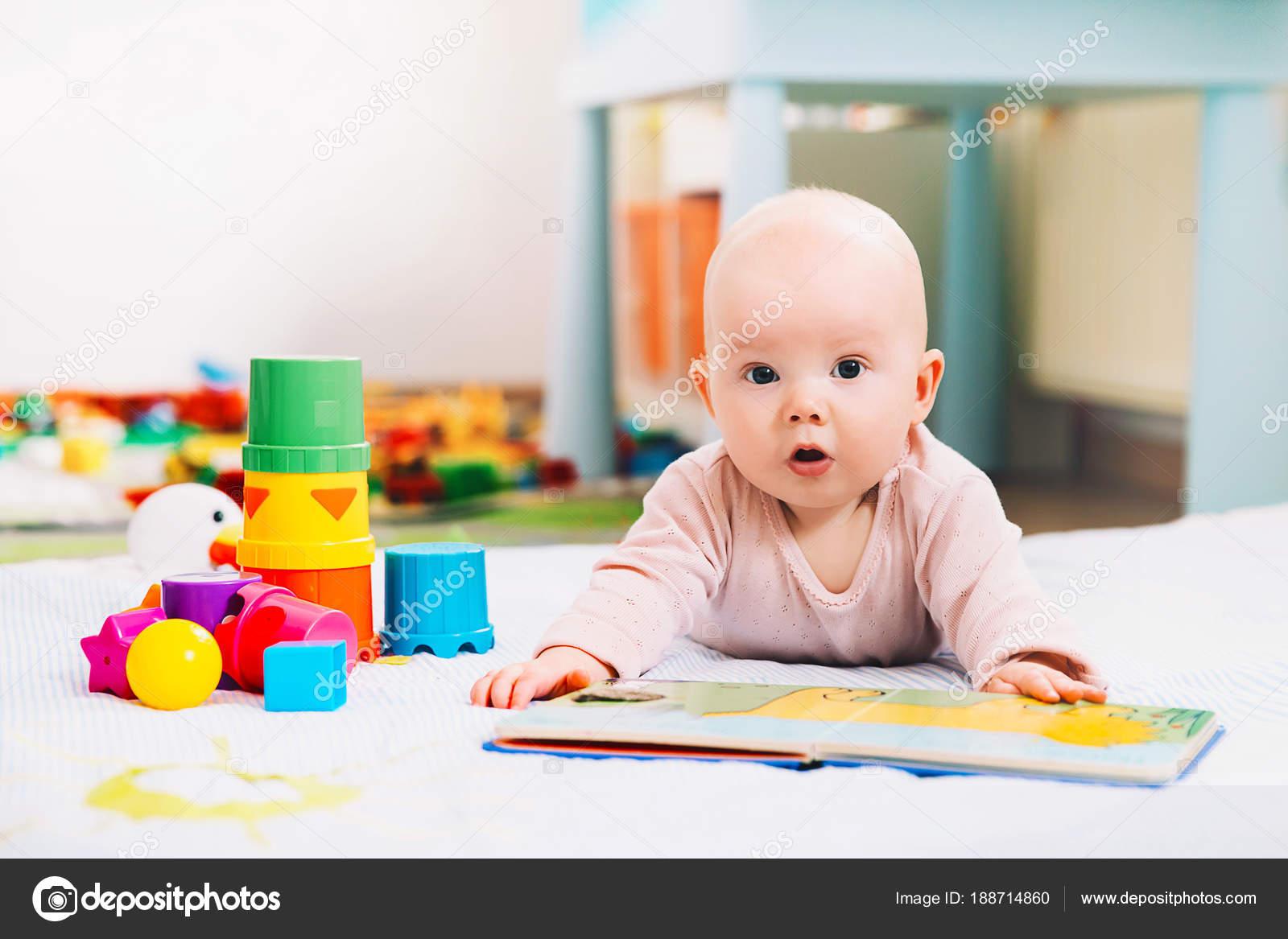 Niedliche Baby Suchen Und Lesen Ein Buch Stockfoto Nataliad