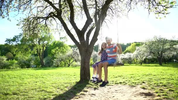 glückliches Geschwisterpaar, das an einem sonnigen Frühlingstag auf der Schaukel schwingt. Statischer Schuss