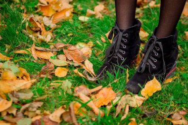 Fall foliage, girl walk on green grass with yellow leaves, boots