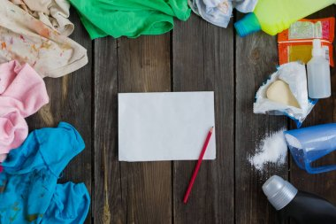 Dirty kids clothing is scattered on a wooden table next to washing powders and white sheet of paper.Concept of searching for information on washing spots, the best means for cleaning clothes.mock up