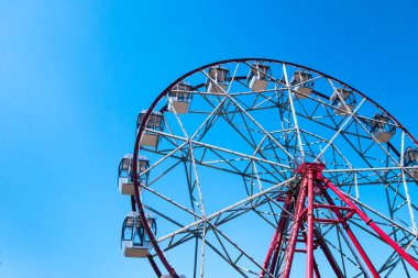 Ferris wheel on a background of clear blue sky. Bright sunny day. The concept of relaxation and entertainment.