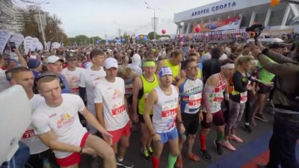 MINSK, BELARUS- SEPTEMBER 15, 2019: A large group of runners are preparing to start at the marathon. Runners warm up before the race