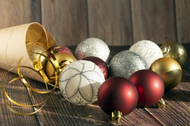 Christmas gifts, gold, silver, red Christmas balls spilled out from a package of kraft paper on a wooden background. Christmas balls. Copyspace