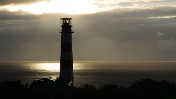 Leuchtturm auf dem Meer unter stürmischen Wolken und mit dem Schiff im Hintergrund