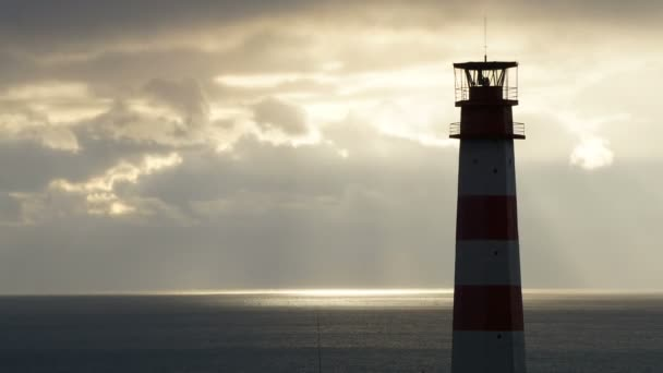 Maják v moři za bouřlivých mračen při západu slunce