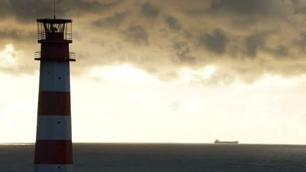 Timelapse maják na moři za bouřlivých mračen a s lodí v pozadí