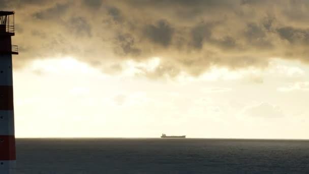 TimeLapse világítótorony a tenger viharos felhők alatt, és a hajó a háttérben