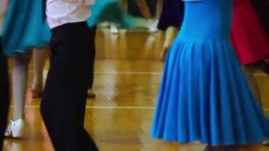 Close-up of legs dancing couples in ballroom.