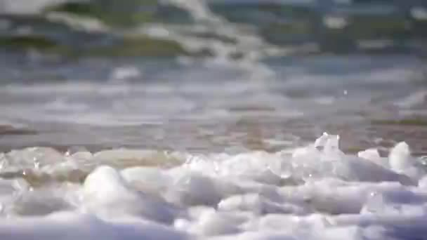 Sparkling wavy water is shining on a sunny day, abstract blurry background at the summer beach