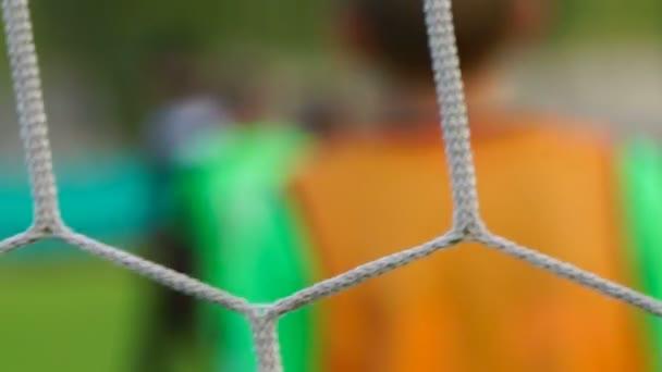 Fotbalový zápas vidět přes net, rozmazané zobrazení