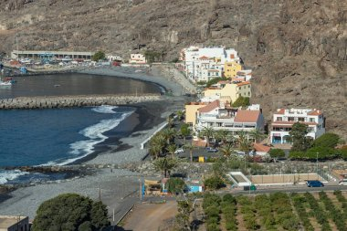 Early morning of quiet warm, sunny weather in the beach and harbor. Aerial view of Playa de Santiago. Panoramic, fisheye lens, wide angle. La Gomera, Canary Islands, Spain