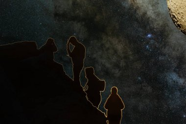 Telephoto long lens shot of Milky Way composed with image of the Moon. Landscape with night sky with stars and silhouette of standing people. Milky way with travelers. Beautiful planet and galaxy.