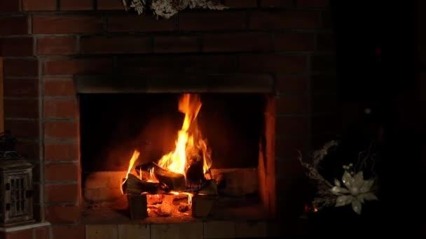 jasně horký oheň hoří v cihlovém krbu. Útulný víkend. Teplo v domě. Odpočinek a relaxace před krbem ve večerních hodinách