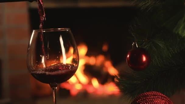 Rotwein wird in einen klaren Weinkelch auf dem Hintergrund der brennenden Flamme des Weihnachtsfeuers gegossen. künstlicher Weihnachtsbaum mit schönen Dekorationen. Neujahrsurlaube mit der Familie