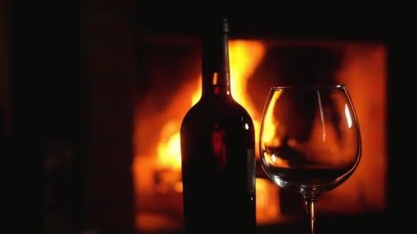 Leere Gläser und eine Flasche Rotwein stehen auf dem Tisch vor dem Kamin vor dem Hintergrund brennenden Holzes im Kamin. Weihnachtsferien im Freundeskreis. Ruhe am lodernden Feuer