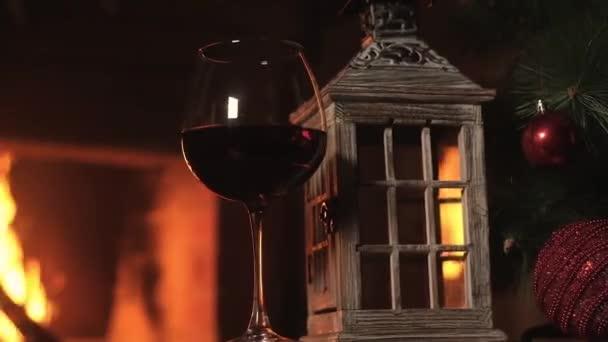 Glas Rotwein mit Holzlaterne Kerzenständer stehen auf dem Tisch vor dem Kamin vor dem Hintergrund des Feuers im Kamin. Weihnachtsbaum mit Dekoration. Neujahrsurlaube mit Freunden