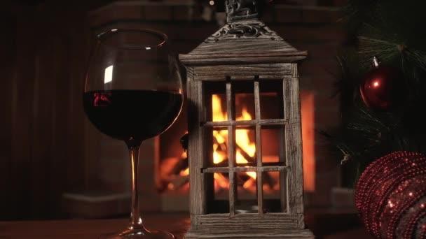 Glas Rotwein mit einem alten hölzernen Kerzenständer auf dem Hintergrund eines brennenden Feuers im Weihnachtskamin. Panorama. Weihnachtsbaum mit Weihnachtsschmuck. Neujahrsurlaube mit Freunden.