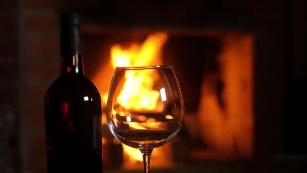 Glas und eine Flasche Rotwein stehen auf einem Tisch vor dem Kamin vor dem Hintergrund brennenden Holzes. Weihnachtsferien im Freundeskreis. Ruhe am lodernden Feuer. Nahaufnahme