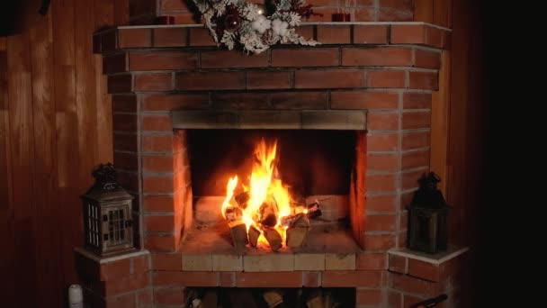 flame of fire burns in brick home Christmas fireplace. festive wreath hangs over fireplace. Wooden candlesticks is decorated with Christmas decor. Rest and relaxation in front of fireplace in evening.