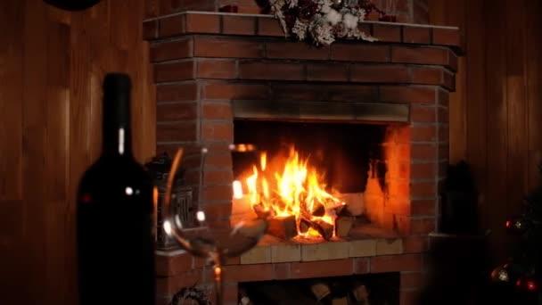 láhev vína a čiré víno sklenice stojí na stole na pozadí hořícího ohně vánočního krbu. Nový rok útulné dovolené s rodinou a přáteli. Panorama natáčení slavnostního interiéru.