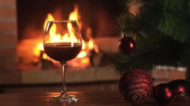 Rotwein im Glas steht auf dem Tisch vor dem Hintergrund der lodernden Flammen des Weihnachtsfeuers. Künstlicher Weihnachtsbaum mit schönen Dekorationen. Neues Jahr gemütliche Ferien mit der Familie