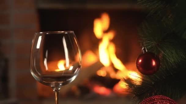 Panoramaaufnahme eines durchsichtigen Weinglaspokals vor dem Hintergrund der brennenden Flamme des Weihnachtsfeuers. künstlicher Weihnachtsbaum mit schönen Dekorationen. Urlaub mit Familie und Freunden.