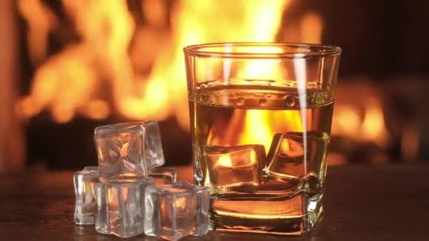 Lassított felvétel Whiskey és jég fél háttér égő tűz a kandallóban.Close - up egy régi öreg ital Üveg az asztalon jégkockákkal a keret közepén. Panoráma.