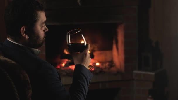 Ruhe am Kamin. Mann im Businessanzug sitzt mit brennender Flamme im Sessel vor dem Kamin und trinkt Rotwein. Gemütliches Wochenende am Feuer. Urlaub oder Party am Kamin. Entspannung mit Alkohol.