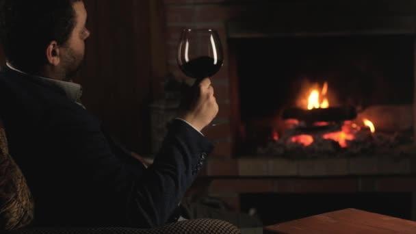 Der erwachsene Mann im Anzug sitzt im Sessel mit einem Glas Rotwein und blickt in den Kamin. Gemütliches Wochenende am Feuer. Urlaub oder Party am Kamin. Ruhigen und genießen Sie Ihren Alkohol trinken