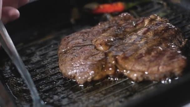 samčí kuchař nalije voňavý olej na kus mramorového steaku na grilovací pánev. Vaření smaženého steaku v restauraci. připravuje v kuchyni škrty. Vaření recepty. lahodné jídlo pro gurmány. zavřít