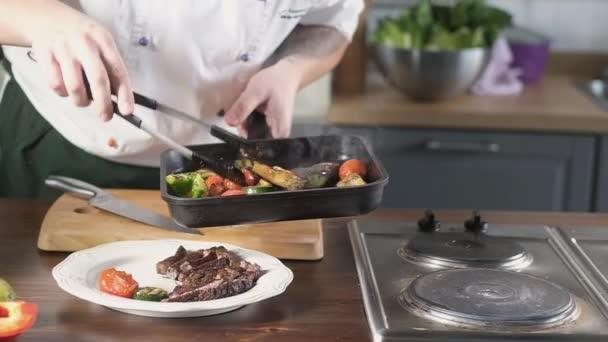 A szakács grillezett zöldséget tesz egy tányérra sült marhahús szűzpecsenyével. séf vesz borsos paradicsom padlizsán a serpenyőben fogóval. A hús mellé. Főzés az étteremben a konyhában