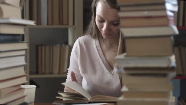 student čte knihy. krásná mladá dívka sedí u knihovního stolu a listuje stránkami knihy. žena čte učebnici mezi mnoha knihami a pije kávu z plastového poháru. Příprava zkoušky.
