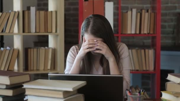 Könyvtári hallgató egy halom könyv között videokonferencián keresztül kommunikál