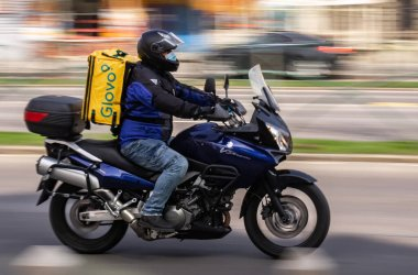Bucharest, Romania - March 25, 2020: A Glovo food delivery courier wearing mask on a motorcycle. Restaurants are closed and only deliveries are allowed during the state of emergency due to coronavirus