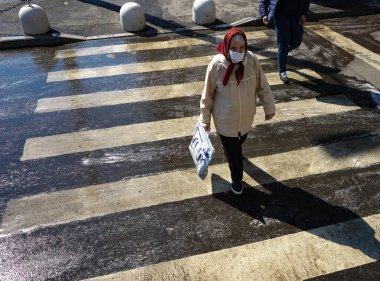 Bükreş, Romanya - 03 Nisan 2020: Maske takan yaşlı bir kadın alışverişe gitti. Romanya koronavirüs nedeniyle tecrit altında ve yaşlıların sabah 11 ile akşam 13 arasında alışveriş yapmasına izin veriliyor