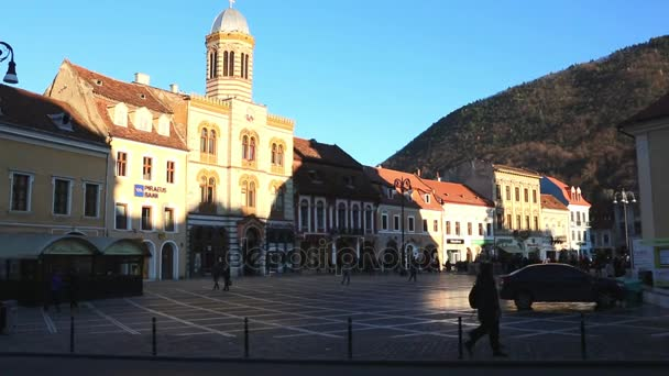 BRASOV, ROMANIA - CIRCA 2015: Bulevardul Eroilor with Transilvania University of Brasov and School Gimanziala Iacob Muresianu in the center of Brasov with people commuting and visiting the city