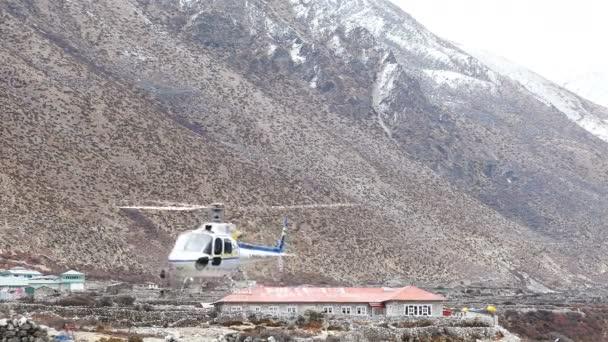 Dingboche, Nepál - duben, 2018: Vrtulník startuje na pozadí budovy s nápisem Everest resort v Dingboche vesnice, Nepál, Himaláje na duben, 2018