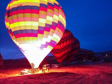 Colorful Hot Air Balloons flying over Cappadocia early morning at winter with dark morning in Turkey