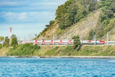 Passenger double deck train moves along the Black sea beach. Sochi. Russia.