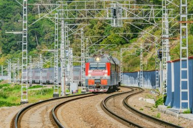 Passenger double deck train moves along the mountains. Sochi. Russia.