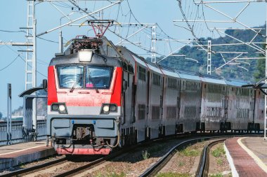 Passenger double deck train moves along the platform by Black Sea.