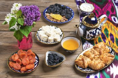 Traditional Uzbek sweets - dried apricot, rohat Turkish delight, raisin, samsa, almond, teapot with tea and bowl with national ornament on wooden table. Flat lay.