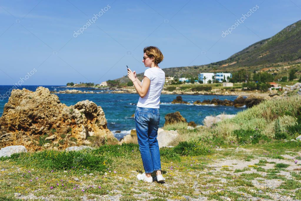 Beautiful girl in jeans on a trip by the sea takes pictures of the landscape on her smartphone for social networks