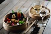 Számos különböző hagyományos kínai dimsum gombóc egy fa kosárban főtt vendégek számára egy fa asztal egy étteremben.