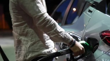 Young man fueling his car at gas station